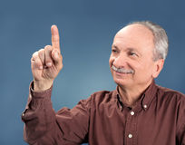 Old man pointing up. Handsome old man pointing up on blue background royalty free stock images