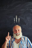 Old man pointing up against blackboard with exclamation mark ins Stock Photos