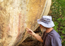 Old man points at bushman rock paintings Stock Photography
