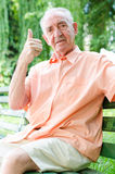 Old man. Portrait of a cute senior man at park sitting with thumb up Stock Photos