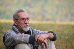 Old man. Portrait of an elderly, worried man with a gray beard and glasses sitting on grass royalty free stock images
