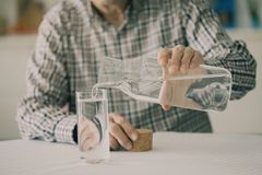 Old man pouring water from bottle to glass in kitchen. Old man pouring water from  bottle to glass in kitchen Stock Images