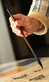 Old man practicing callingraphy using a brush pen Royalty Free Stock Photos