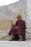 The old man with the prayer wheel. Indian old man with the prayer wheel on the threshold of the temple stock images