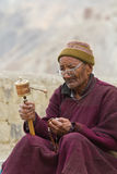 The old man with the prayer wheel Royalty Free Stock Image