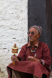 The old man with the prayer wheel Royalty Free Stock Images