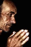 Old man praying. Wrinkled and sun burned skin stock photography