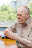 Old man praying. At home near the window Stock Photos