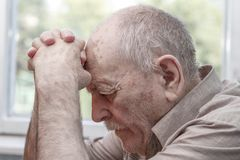 Old man praying. At home near the window Royalty Free Stock Images