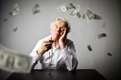 Old man is praying with rosary beads. Falling dollar banknotes. Old man is praying with wooden rosary beads. Falling dollar banknotes. Currency, prayer and Royalty Free Stock Photos