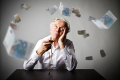 Old man is praying with rosary beads. Falling Euro banknotes. Old man is praying with wooden rosary beads. Falling Euro banknotes. Currency, prayer and mercy Stock Photo