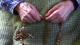 Old man praying rosary stock video footage