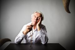 Old man is praying with rosary beads. Prayer and temptation. Old man is praying with wooden rosary beads and devil as snake. Prayer and temptation concept royalty free stock images