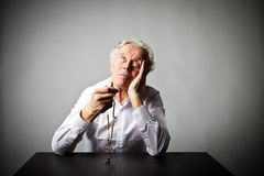 Old man is praying with rosary beads. Old man is praying with wooden rosary beads royalty free stock images
