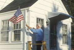 Old Man Putting American Flag on House, Stonington, Maine Stock Image