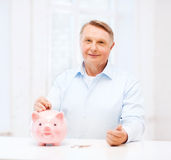Old man putting coin into big piggy bank Royalty Free Stock Images