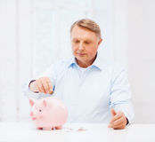 Old man putting coin into big piggy bank. Savings, oldness,business and banking concept - old man putting coin into big piggy bank Royalty Free Stock Photo