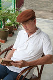 Old man reading. Old man sitting on the chair reading the book Royalty Free Stock Image