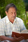 Old man reading book. Healthy looking old man is his late 70s sitting in garden at home and reading book Stock Photo