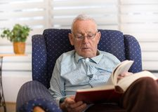 Old man reading book at home. Portrait of serious old man reading book in armchair at home Stock Photography