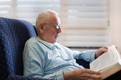 Old man reading book at home. Portrait of serious old man reading book in armchair at home Stock Image
