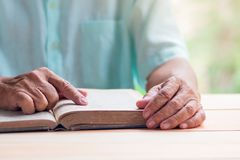 Old man reading book on light brown wooden table surface, pointing with right index finger Royalty Free Stock Photography