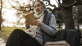 Old man reading book in the park royalty free stock photo