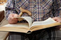 Old man reading a book Stock Images