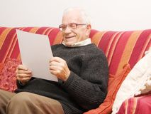 Old man reading a financial report Stock Photo