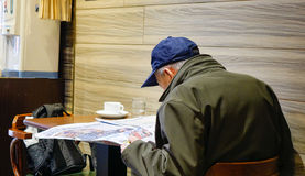 An old man reading news at the coffee shop in Taipei Stock Photos