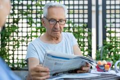 Old man reading newspaper royalty free stock photo