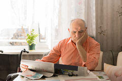 Old Man Reading Newspaper with Hand on Face Stock Photos