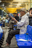 Old man reading newspaper at the Happy Valley Racecourse Stock Images
