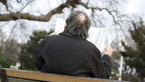 Old man reading newspaper in the park royalty free stock image