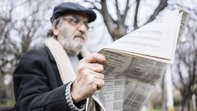 Old man reading newspaper in the park stock image
