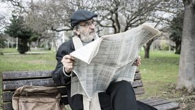 Old man reading newspaper in the park royalty free stock photos