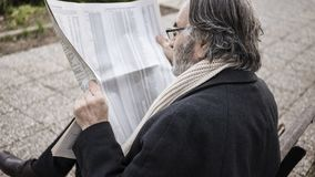 Old man reading newspaper in the park stock photography