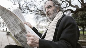 Old man reading newspaper in the park stock photo