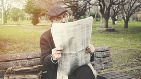 Old man reading newspaper in the park royalty free stock photo