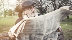 Old man reading newspaper in the park royalty free stock photography