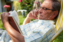 Old man reading outdoor. Healthy looking old man is his late 70s sitting in garden at home and reading book, outdoor Stock Photos