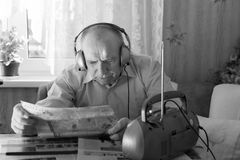 Old Man Reading Tabloid While Listening Music. Close up Old Bald Man Reading Tabloid at the Table in Living Room While Listening Music at the Radio with Headset Royalty Free Stock Photos