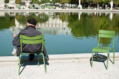 Old man reading in Tuileries garden in Paris Royalty Free Stock Image