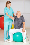 Old man during rehab in physiotherapy Stock Photo