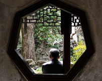 Old man relaxing in traditional Chinese garden royalty free stock photo