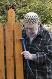 Old man repairing a gate Royalty Free Stock Image