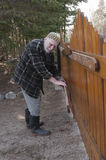 Old man repairing a gate stock photography