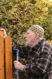 Old man repairing a gate royalty free stock photos