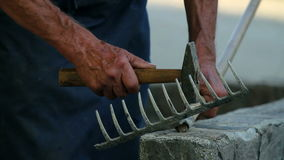 Old man repairing wooden rake stock video footage