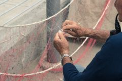 Old man reparing fishing net. Old fisherman reparing fishing net, sitting with pipe in his mouth royalty free stock photos